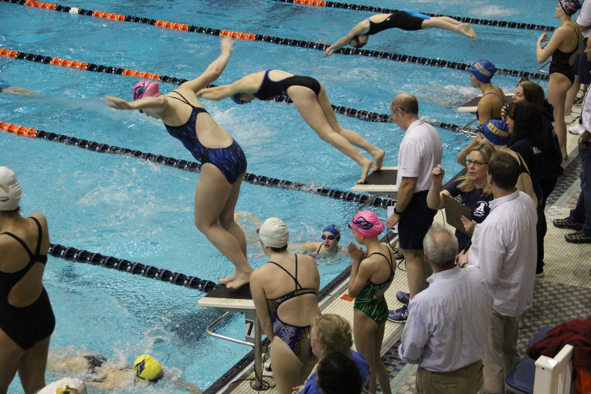 Warriors dive into the water during a relay.