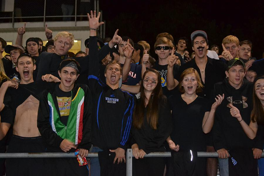 A group of seniors cheering on their team from the front row