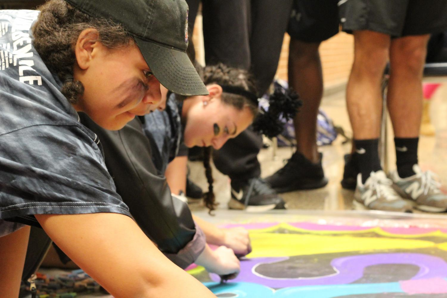 Deija Brooks and Kira Repich coloring the senior mural.