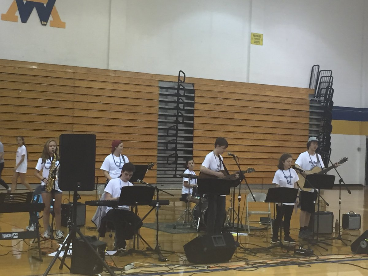 The members of Unintended Consequences perform at Why I Run.  From left to right: Kirsten Casteel (saxophone), Alex Benson (bass), Eamon Dougherty (keyboard), Kathleen Hughes (drummer), Zach Thorne (guitar), Illiana Roèsso (lead vocals), and Josiah Luftig (guitar).