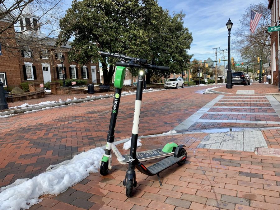 Rival e-scooters Lime (left) and Bird (right) parked in Charlottesville's Court Square.