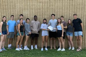 Changing of the guard: outgoing Executive Council passes The Notebook to the newly elected EC. From left: new members Carly Hegemier, Michael Mitchell, Tate Kessler, Austin Winslow, Elke Beaumont, Jaiden Beckett-Ansa, and Nicole Bilchick receive The Notebook from graduating seniors Matthew Gustafson-Missett, Baylee Hughes, Hayes Hegemier, Anna Snyder, and Andrew Sime.